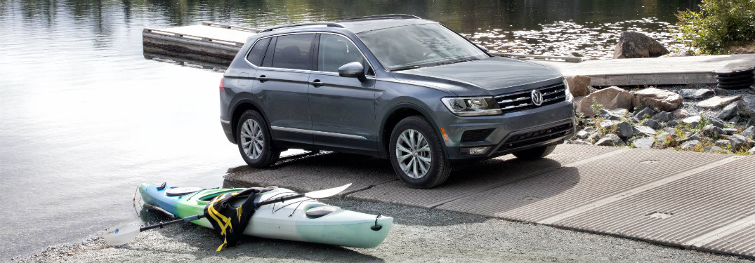 gray volkswagen tiguan with kayak on the ground