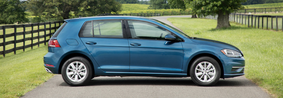 blue volkswagen golf on road by fence