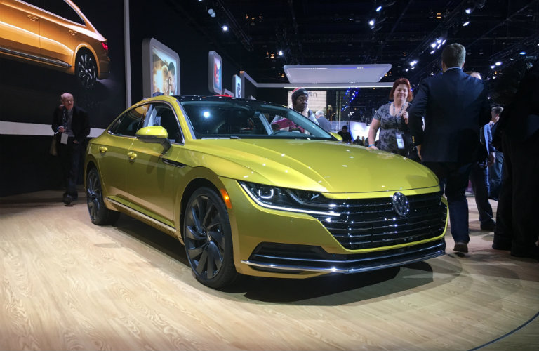 golden volkswagen arteon on display