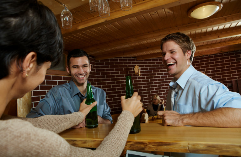 two men happy at bar as bartender serves them beers
