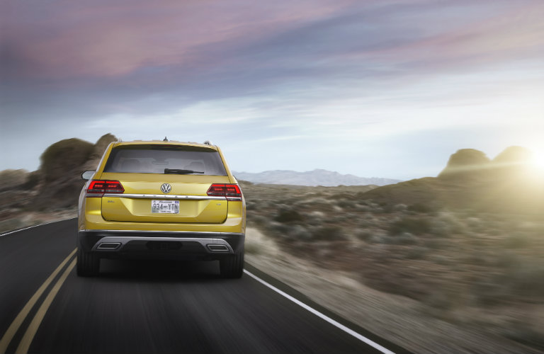 rear view of gold volkswagen atlas driving on road