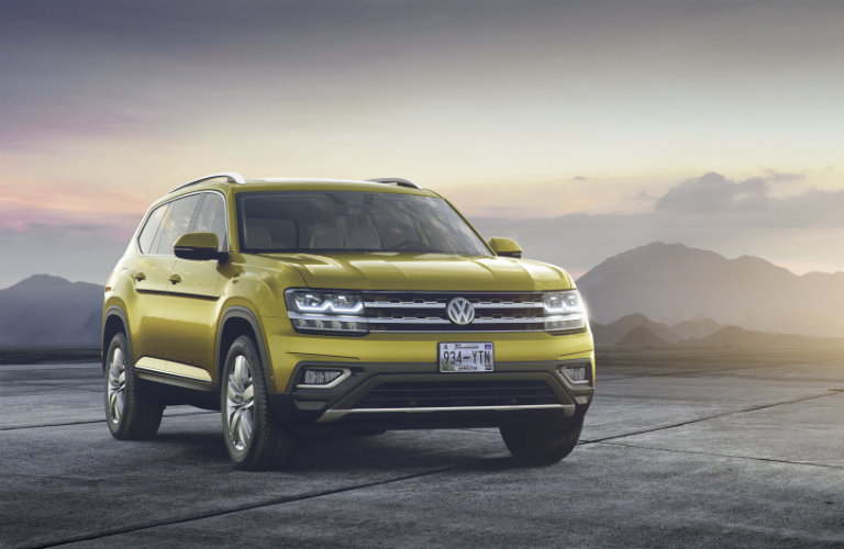 front view of gold volkswagen atlas in front of mountains