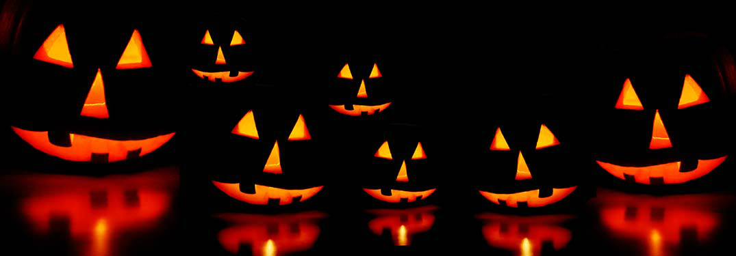 A row of lit jack-o'-lanterns at night