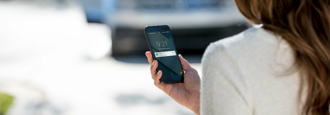 Woman holding a phone with the Volkswagen Car-Net app
