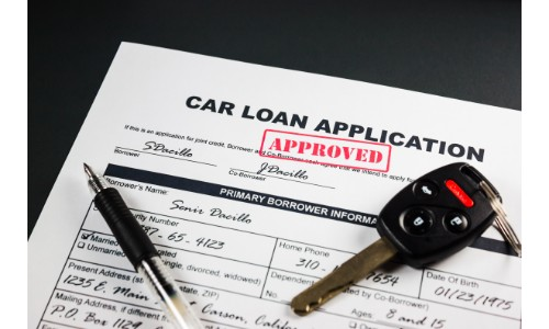 Approved car loan with a key and pen