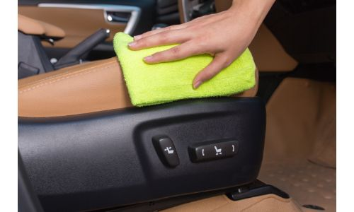 Hand wiping down the center console of a vehicle