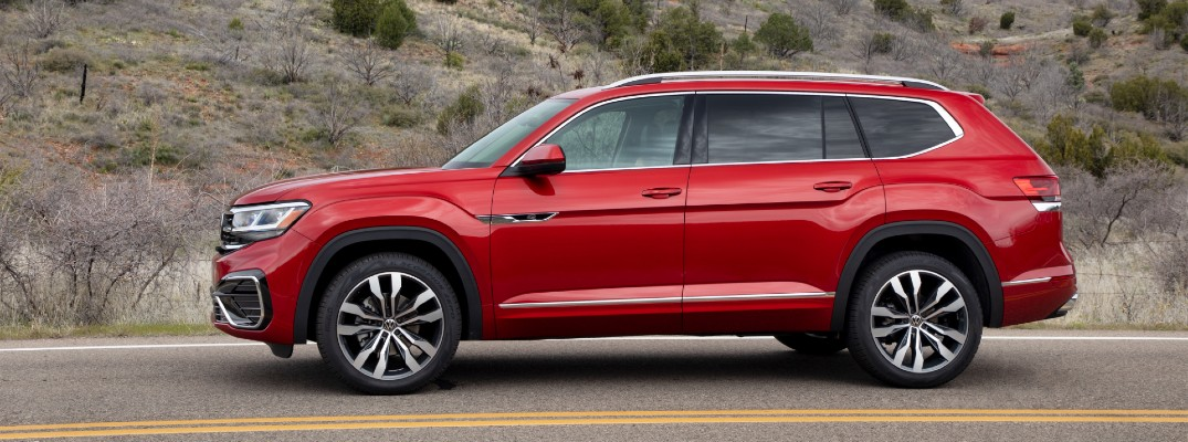 2021 Volkswagen Atlas driving past a dusty hill