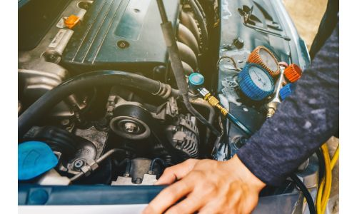 stock photo of mechanic waiting on refrigerant to recharge