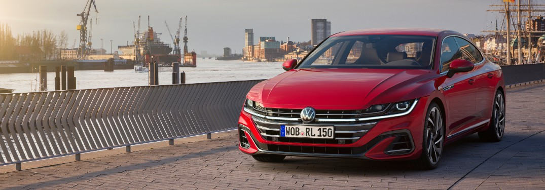 2021 Volkswagen Arteon exterior shot in red paint color parked alongside a river on a cobblestone road