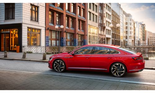 2021 Volkswagen Arteon exterior side shot with red paint color parked on a bridge between cobblestone paths