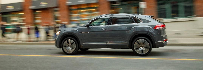 2020 Volkswagen Atlas Cross Sport SEL Premium R-Line model with Pure Gray paint color exterior side shot driving through a city