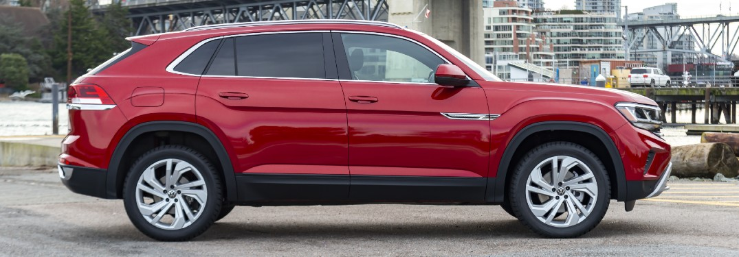 2020 Volkswagen Atlas Cross Sport exterior side shot with Aurora Red Metallic paint color parked on a concrete lot near a river