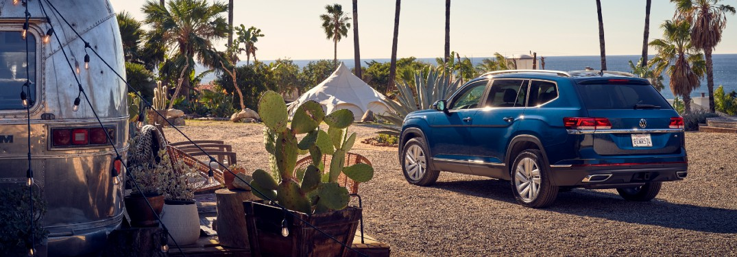 2021 Volkswagen Atlas SEL exterior shot with dark blue paint color parked by a trailer on the beach