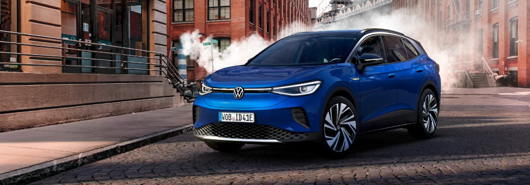 2021 Volkswagen ID.4 exterior shot with blue paint color parked on a cobblestone road with fog and brick buildings in the background
