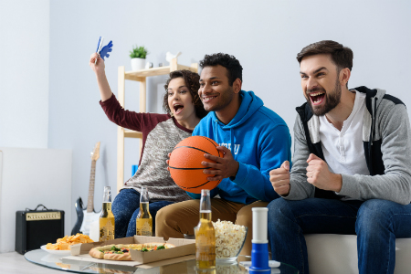 three basketball fans on couch watching the game