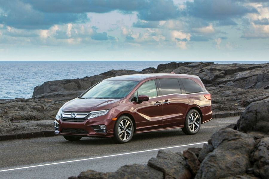 Red 2020 Honda Odyssey driving by ocean through rocks exterior front driver side
