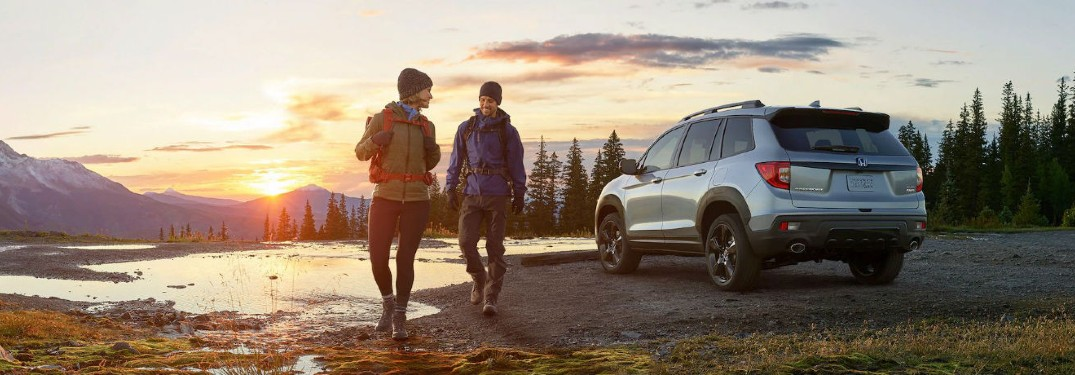 2020 Honda Passport AWD rear driver side couple walking away in hiking gear in forest by lake