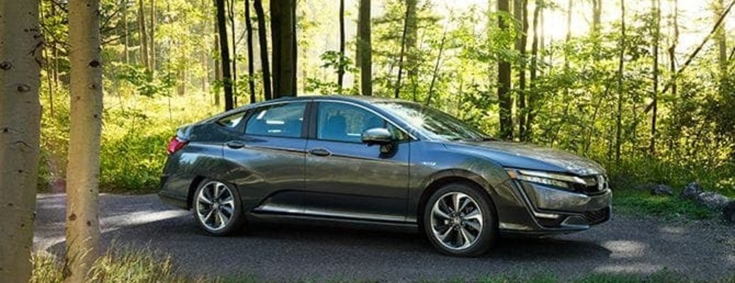 2020 Honda Clarity grey exterior passenger side on paved forest road