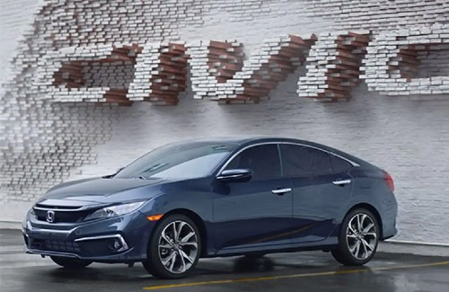 2021 Honda Civic Sedan dark blue exterior front fascia driver side parked in front of wall that says civic