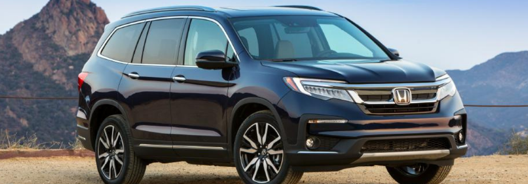 2022 Honda Pilot parked on a dirt road with mountains in the background