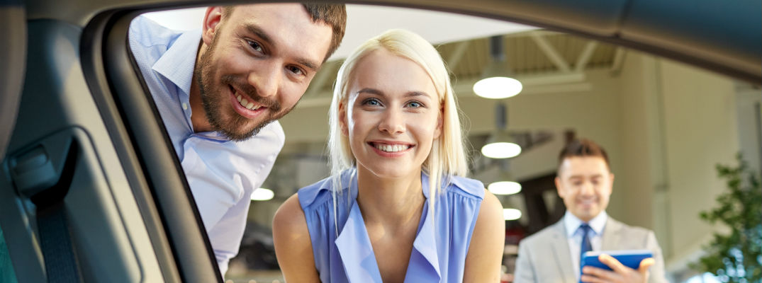 A stock photo of a young couple looking at buying a new car.