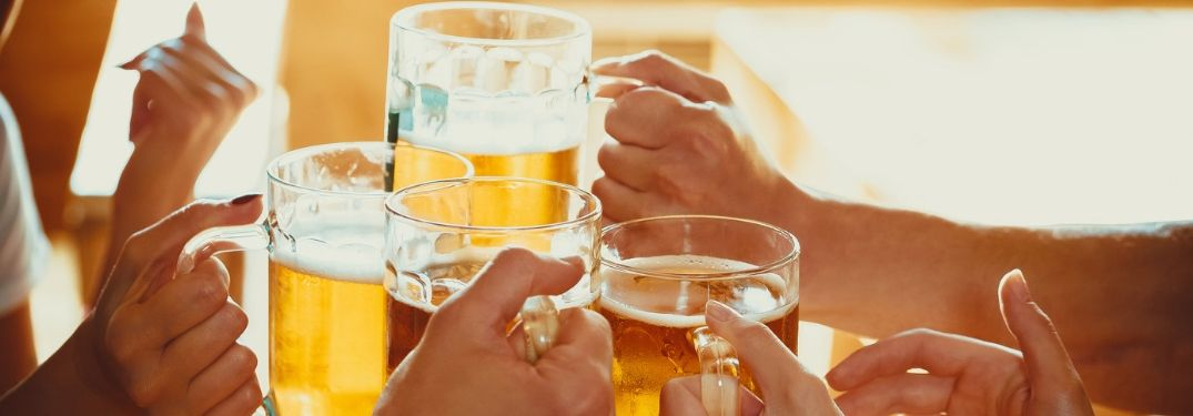 group of friends clinking beer glasses together