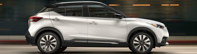 side profile view of white 2018 Nissan Kicks driving down a road