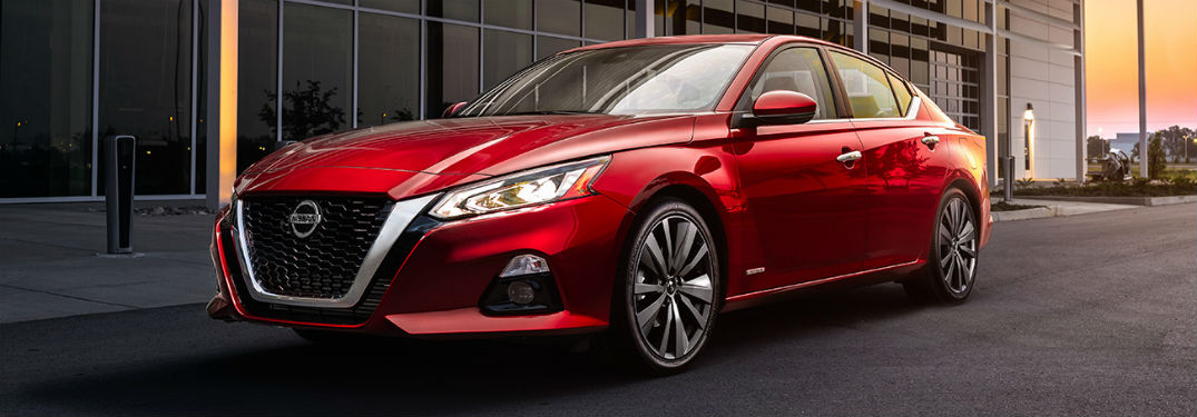 2019 Nissan Altima exterior front fascia and drivers side in front of building with glass windows