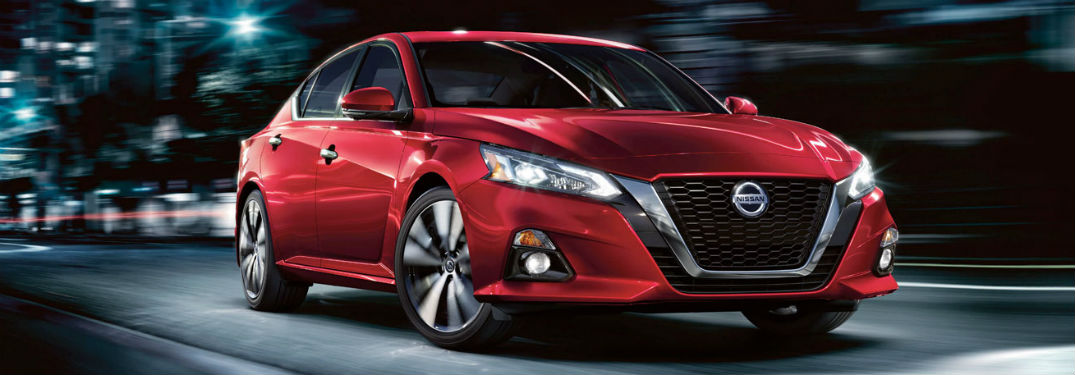 2020 Nissan Altima red exterior front fascia passenger driving through city at night