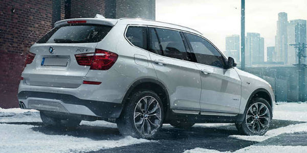 White 2017 BMW X3 Rear Exterior On Snowy Road With City Skyline In Background