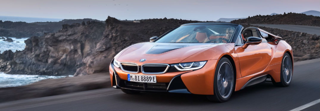 Orange 2019 BMW i8 Roadster on Coast Road with Cliffs and Water in Background