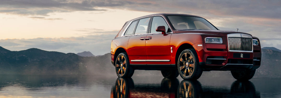 Red 2018 Rolls-Royce Cullinan on Wet Sand with Mountains in the Background