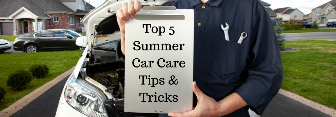 Mechanic in Blue in Front of a White Car Holding a Clipboard with Black Top 5 Summer Car Care Tips & Tricks Text