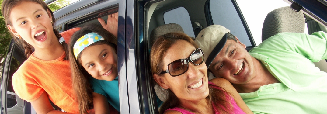 Family Sitting in a Gray Car and Smiling