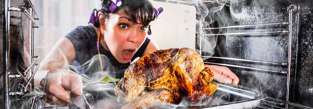 Woman Taking Burnt Turkey Out of the Oven