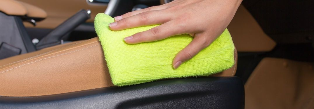 Close Up of Woman Using a Yellow Rag to Clean a Car Interior