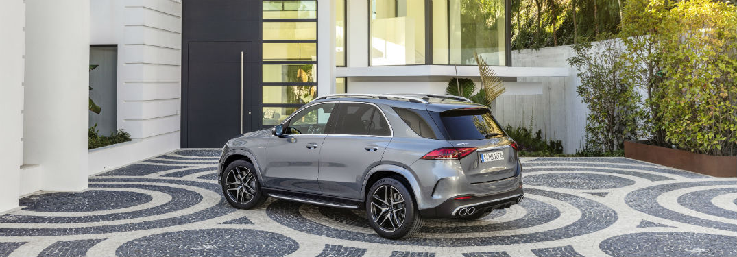 2021 MB AMG GLE 53 exterior front fascia and drivers side in front of house with shrubbery