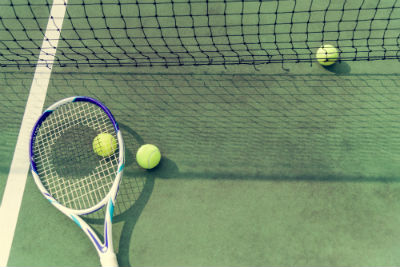 Tennis racket and tennis balls on tennis court