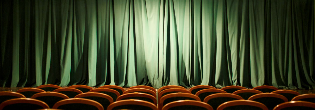 Theater stage green curtains red chairs