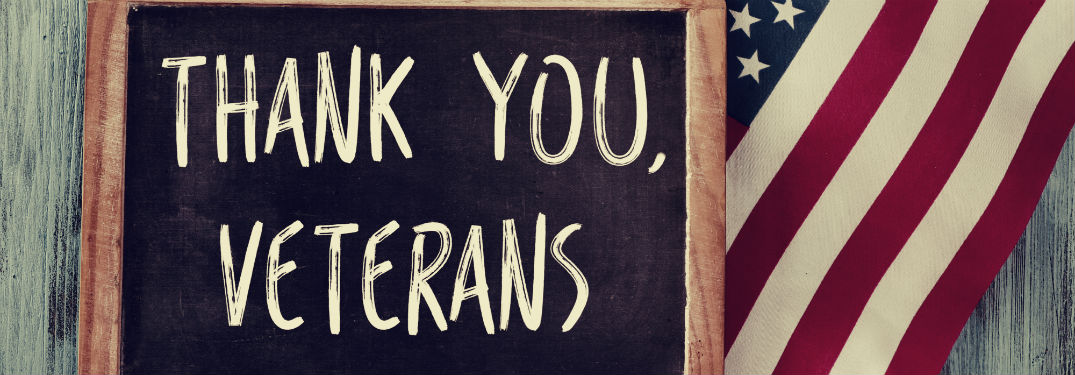 Thank you veterans written on chalkboard with flag behind it