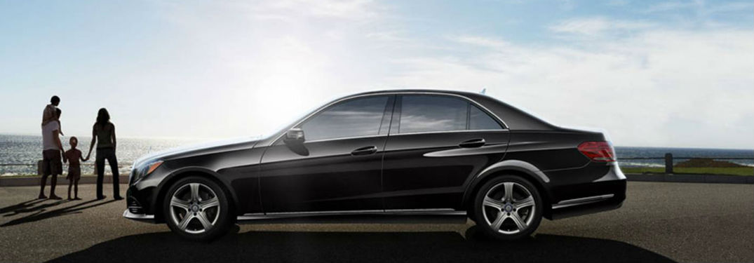 2016 MB E-Class sedan driver side profile with family on beach