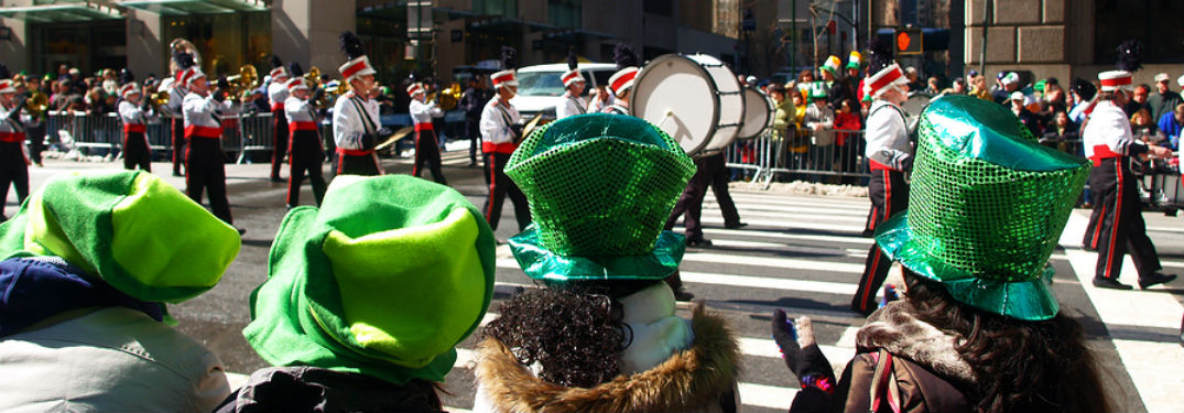 4 People in green hats watching NY St Patrick's Day Parade band