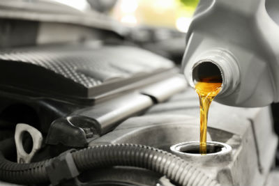 Bottle of engine oil being poured into vehicle