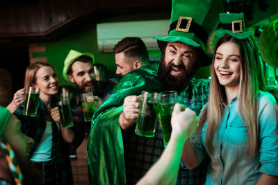 Enthusiastic people celebrating St Patricks Day with green beer and in green hats