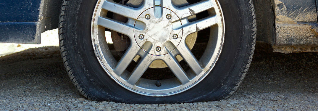 Flat tire on gravel road close up