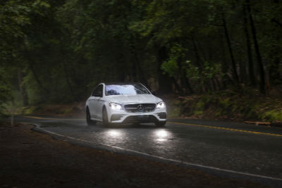 2019 MB E-Class exterior front fascia and passenger side on dark road with headlights on