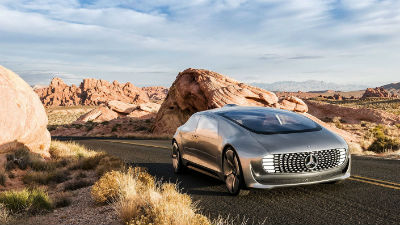 2020 F 015 exterior front fascia and passenger side driving around corner of desert road