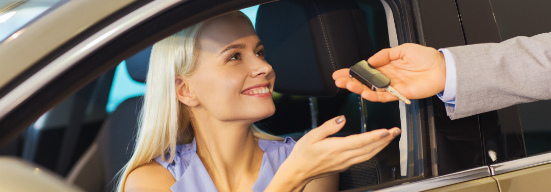 woman in car being handed keys