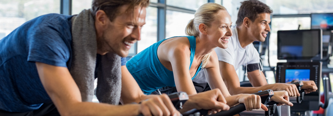 group of people exercising on stationary bikes together