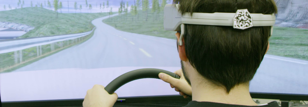 man using nissan brain-to-vehicle technology in driving simulator